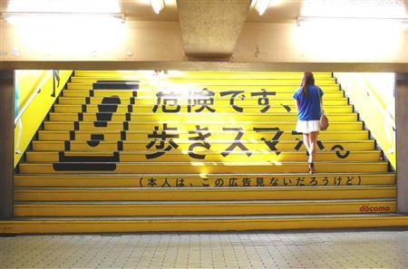 ドコモが新宿駅構内に設置した歩きスマホ防止の広告。 階段に貼ることで注意喚起している。