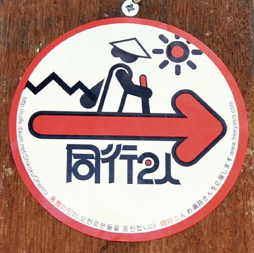 ステッカーは直径10センチの円形などバリエーションがある。札所への道順を示す矢印のほか、日本語とハングルで「同行二人」「お遍路さんを応援します」と記されている。