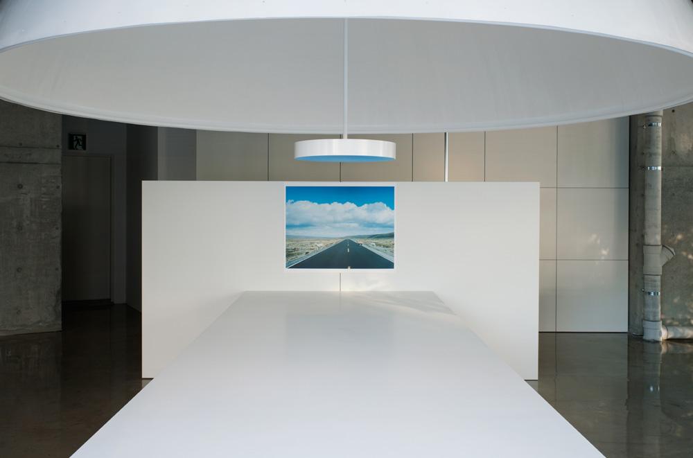 白い照明と白い机と壁に掛けられた一直線に伸びる道の写真。 引用元:http://www.archdaily.com/271614/mr_design-office-schemata-architects 写真:Takumi Ota